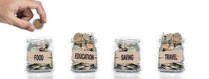 Dinheiro que recolhe, mão que põe a moeda no frasco de vidro Dinheiro da economia para alimentos, educação, futuro e curso Fotografia de Stock Royalty Free