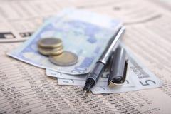 Dinheiro real sobre o jornal financeiro Fotografia de Stock Royalty Free