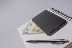 Dinheiro, telefone esperto, pena e caderno na tabela do escritório no fundo branco Conceito do orçamento Imagem de Stock Royalty Free