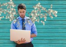 dinheiro texting Homem de negócios novo com portátil Dinheiro que vem acima do portátil imagens de stock royalty free