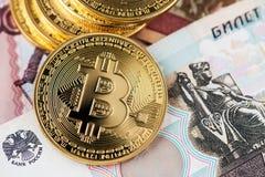 Dinheiro virtual de Bitcoins em cédulas do russo Imagem ascendente próxima dos bitcoins com as cédulas dos rublos de russo fotografia de stock royalty free