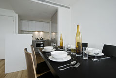 Dining aea. Modern luxury dining area with open plan kitchen in the background Royalty Free Stock Photo