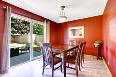 Dining area with bright red walls and walkout patio Stock Photos