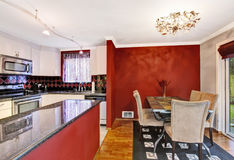 Dining area connected to kitchen with red walls, vintage chandelier. Stock Image