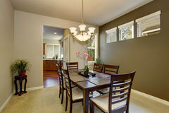 Dining area with deep brown table set and carpet floor Stock Images