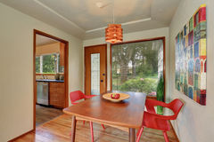Dining area interior with red chairs and exit to the back yard. Stock Photos