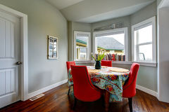 Dining area with red soft chairs and hardwood floor. Royalty Free Stock Photo