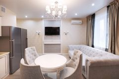 Dining area with TV and sofa - light, light interior. Electric Lighting Royalty Free Stock Images