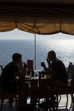 Dining on board of cruise ship. Two silhouettes of men taking dinner at a restaurant of a cruise ship having a view of the open sea Royalty Free Stock Image