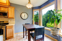 Dining breakfast table near the kitchen with blue walls. Stock Photo