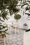 Dining in the courtyard. Image of romantic greek restaurant in courtyard with olive trees Stock Photo