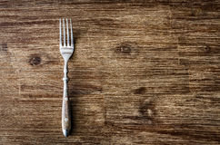 Dining fork on vintage wooden table Stock Photos