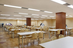 Dining hall. Carefully arranged chairs and tables in a modern dining hall Stock Image