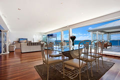 Dining & Living Room. Spacious dining area and the living room in a luxurious waterfront home Royalty Free Stock Images