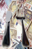Dining out knife and fork isolated in money. Fork and knife isolated against a money background with a clipping path as in cost of eating out stock photography