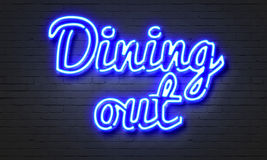 Dining out neon sign on brick wall background. Stock Images