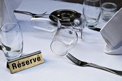 Dining out reserved. Reserved restaurant table white table cloth and napkins beverage glasses forks ashtray. eating out restaurants meetings pleasure Essen gehen stock photos