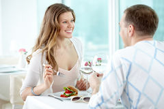 Dining out. Two happy valentines sitting in cafe and enjoying each other Royalty Free Stock Photos