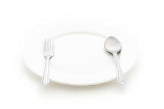Dining place setting. A white plate with silver fork and spoon Stock Photography