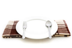 Dining place setting. A white plate with silver fork and spoon Stock Images