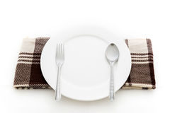 Dining place setting. A white plate with silver fork and spoon Stock Photos
