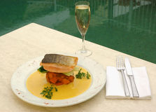Dining by the pool. A meal by the pool of salmon and wine at a luxurious restaurant stock photos