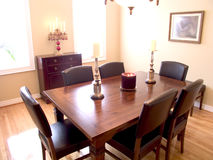 Dining Room 03. Dining Room with dark wood table, six chairs, candelabra and two windows with a natural wood floor royalty free stock photo