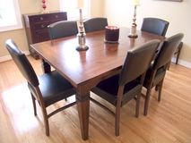 Dining Room 03. Dining Room with dark wood table, six chairs and two windows with a natural wood floor royalty free stock photography