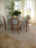 Dining Room. Beautiful bright dining room with table and six blue chairs, room has tile floors with a rug, white drapes and etched glass windows Stock Photography