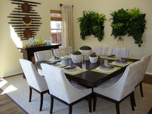 Dining Room. Beautiful bright dining room with table and eight chairs, room has wood floors and a rug. Plants hanging on wall, wood bar stock photo