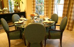 Dining  room. Delightful dining room with tiled floor,round glass table and chairs, drapes and buffet Royalty Free Stock Photography