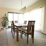 Dining room. Elegant and simple dining room. Vertical blinds on the windows. Natural daylight pouring in.Table and six chairs Stock Images