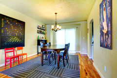 Dining room with black table and grey rug with green walls. Royalty Free Stock Images