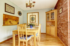 Dining room with brick wall and corner cabinet Stock Images