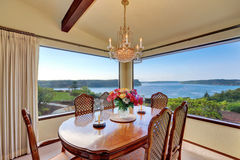 Dining room with carved wood table set and water view Stock Photo