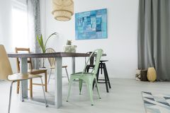 Dining room with communal table. Chairs, lamp and window curtain Stock Photos