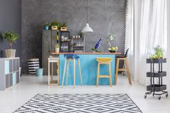 Dining room with communal table. Patterned carpet and plants in bright dining room with wooden stools at communal blue table, under a lamp Stock Images