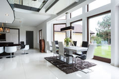 Dining room connected to the kitchen. The bright dining room connected to the kitchen in the residence Royalty Free Stock Photos