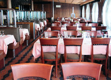 Dining room on cruise ship. A view of rows of tables and chairs inside a dining room aboard a cruise ship Stock Images