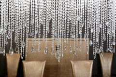 Dining room crystal lamp golden chairs Stock Images