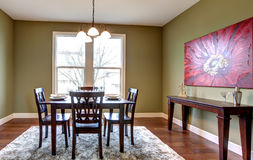 Dining room with green walls and red painting. Stock Image