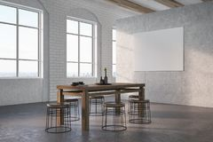 Concrete and brick dining room, poster. Dining room interior with concrete and white brick walls, large windows, a concrete floor and a dark wooden table with Royalty Free Stock Photos