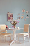 Dining room interior with flowers decorative plates blue wall an Stock Image