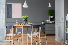 Dining room interior. Grey dining room interior with pink and blue painting, wooden table and chest of drawers stock photos