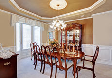 Dining room interior in luxury house. Beautiful dining room interior in luxury house. Wooden dining table set blend perfectly with  light brown walls and white Royalty Free Stock Photography