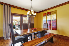 Dining room interior. Rustic wooden table, bench and high-back chairs. Royalty Free Stock Image