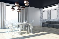 Marble dining room corner, posters. Dining room interior with white marble walls, a wooden floor, loft windows, a long table with white chairs, a sofa and Stock Photos