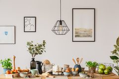Dining room with wooden table. Dining room interior with white wall, art prints and a wooden table with bread and fruit Royalty Free Stock Photos