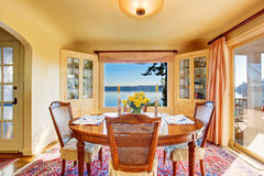 Dining room interior with wooden table set. Amazing water view. Stock Image