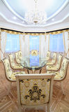 Dining room with luxury gilt furniture and beautiful table. With glass top in classic style Stock Image